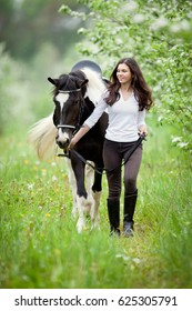 Young woman and pinto horse in apple garden. Horse and beautiful lady walking outdoor. Horse rider.