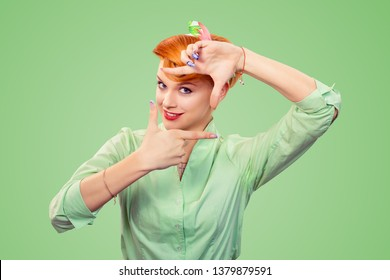Young woman, pinup retro hair style girl making framing key gesture with hands isolated over green background