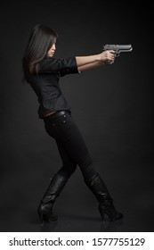 Young woman with pistols in black clothes over dark background at studio