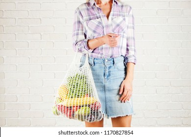 Young woman in plaid shirt, jeans skirt with bag of mixed fruit, vegetables: corn cob, tomato, pepper, lettuce salad, pear & apple. Zero waste concept. White brick wall copy space background, close up