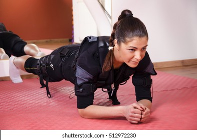 Young woman, plank exercise on muscle stimulator