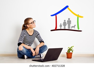 Young woman planning new house design sitting on the floor with laptop. Concept of family real estate and mortgage.