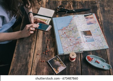 Young woman plans trip on map using pins, red rope and smartphone. Girl gets inspired with photos of nature on dark wooden table