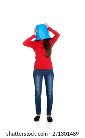Young woman with plastic bucket on head.