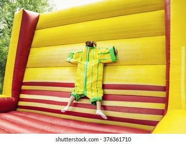 Young woman in plastic dress in a bouncy castle imitates a fly on velcro wall. Inflatable attraction. Leisure activity.