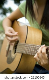 A young woman playing an acoustic guitar