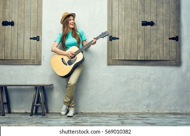 Young woman playing acoustic guitar. Full body portrait.