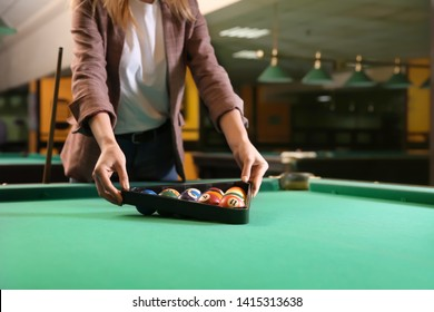 Young woman playing billiard in club