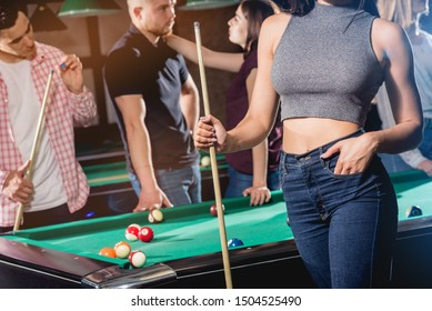 Young woman playing in billiard. Posing near the table with a cue in her hands. A group of friends on the background.