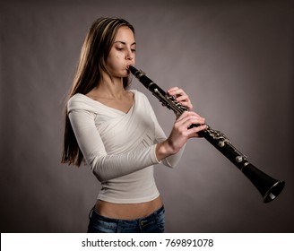 young woman playing a clarinet on a gray background