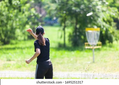 Young woman playing flying disc sport game in the park