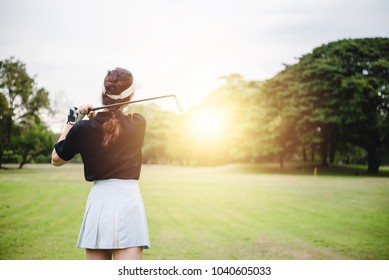 Young woman playing golf on a golf course on a bright morning the park. Exercising and Healthcare Concept.