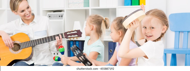 Young woman playing the guitar close to the three girls with tambourines with the case full of toys behind them
