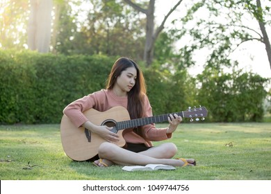 Young Woman playing guitar on nature background and sing a song from Christian hymn book.