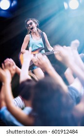 A young woman playing guitar on stage during a concert outside, the fans have their arms up. Shot with flare