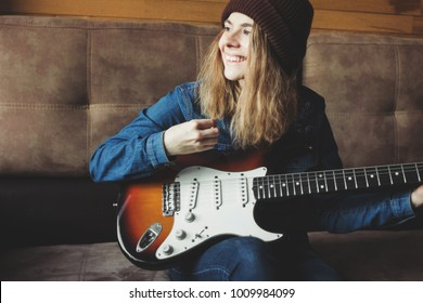 Young woman playing guitar and smiling. Music concept. Home atmosphere on background.