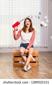 Young woman playing with her banknotes spreader machine happily