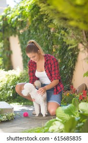 Young woman is playing with her dog in front or back yard