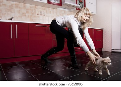 Young woman playing with a kitten on red kitchen