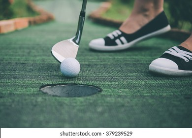Young woman is playing mini golf. Toned picture