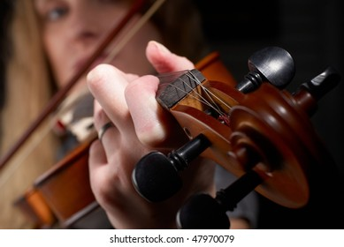 Young woman playing on violin on dark background