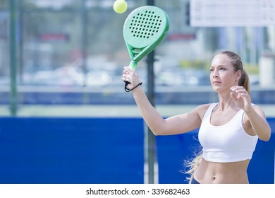 young woman playing a paddle match is ready to hit the ball in an outdoor court outdoor - focus face