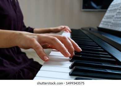 Young woman playing piano. Close up hands on the synthesizer keyboard
