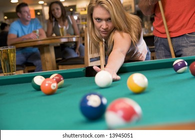 Young woman playing pool in a bar