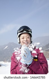 Young Woman Playing with Snow in Ski Resort