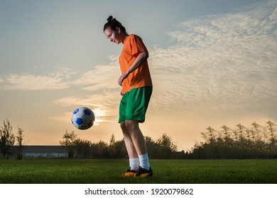 Young woman playing with a soccer ball in sprts field