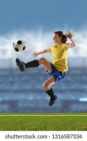 Young woman playing soccer inside large stadium