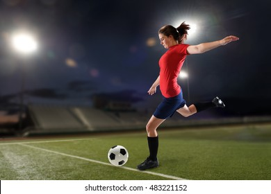Young woman playing soccer inside a stadium at night