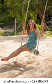 young woman playing the swing on beach