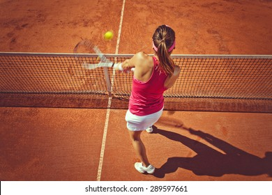 Young woman playing tennis.High angle view.Backhand volley.