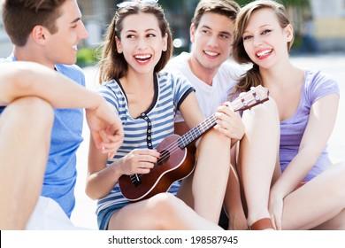 Young woman playing ukulele friends