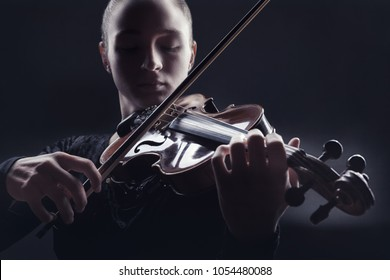 Young woman playing the violin against a dark background. Studio shot