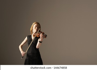 Young woman playing the violin against gray background