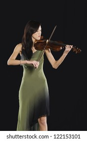 Young woman playing violin isolated over black background