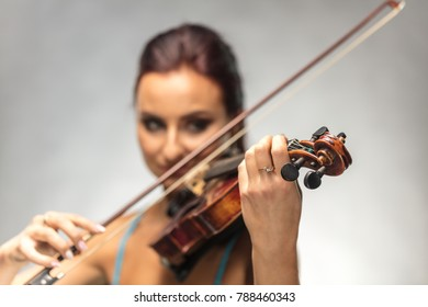 Young woman playing a violin on a gray background