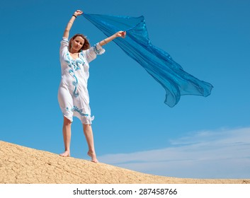 young woman playing with the wind in the desert