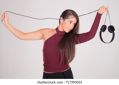 young woman plays with headphones in hands