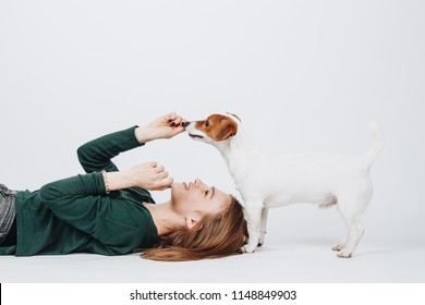 Young woman plays with her jack russell terrier dog isolated on white background. Girl lies down and looks up on her dog. Owner and dog have fun. Studio portrait.