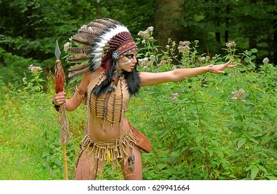 A young woman plays the part of a native American Indian.She dresses up as an Indian warrior and wears a feathered headdress, posing outdoors for the camera .