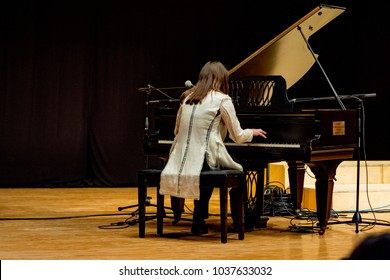 young woman plays piano