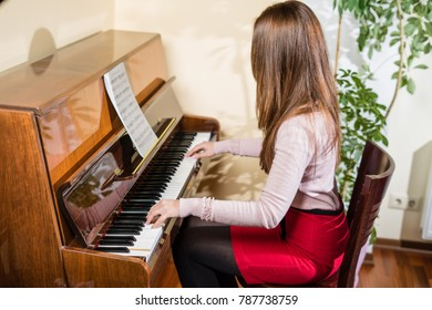 a young woman plays the piano with all the music in front