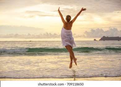 Young woman plays at the sea