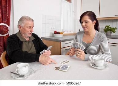 A young woman plays with seniors in their free time with playing cards
