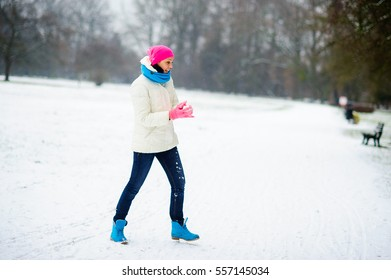 Young woman plays with someone in snowballs. To the woman it is very cheerful. In the winter park all ground is covered with snow. Winter games with the snow give joy.