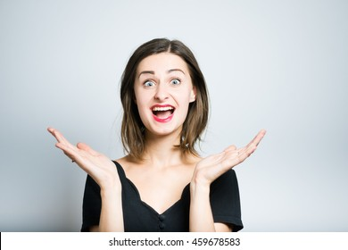 young woman pleasantly surprised studio photo isolated on a gray background