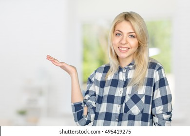 Young woman pointing at blank wall